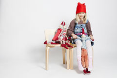 Young girl playing with toy Christmas elf dolls Stock Photos
