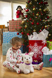 Young girl playing with toy dog in front of Christmas tree. Royalty Free Stock Image