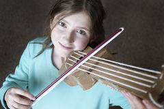 Young Girl Playing Toy Violin Stock Photography