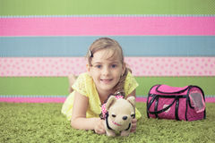 Young girl playing with toys on the carpet Stock Photography