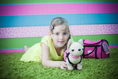 Young girl playing with toys on the carpet Royalty Free Stock Photo