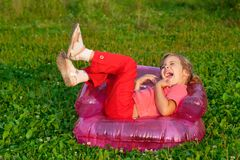 Young girl playing tricks in inflatable armchair Royalty Free Stock Photography