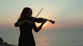Young girl playing the violin at the background stock video footage
