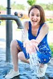 Young girl playing with water squirt and making splashes royalty free stock photo
