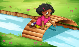 A young girl playing at the wooden bridge Royalty Free Stock Photo