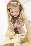 Young Girl Playing With Wooden Building Blocks In Bedroom Stock Photography