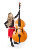 Young girl plays double bass in studio Royalty Free Stock Images