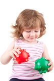 Young girl plays with her two piggy banks. Picture of a toddler playing with her two colored piggy banks Stock Photos