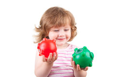 Young girl plays with her two piggy banks. Picture of a toddler playing with her two colored piggy banks Royalty Free Stock Photos