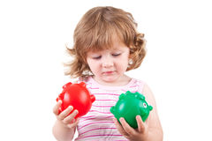 Young girl plays with her two piggy banks. Picture of a toddler playing with her two colored piggy banks Stock Photography