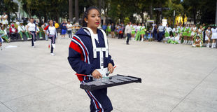 Young girl plays lyre in a march band. A young teenager girl playing a silver lyre in a march band in a local event in toluca mexico Royalty Free Stock Photography