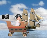 Children Play Pirate, Pretend, Make Believe. A young girl plays make believe and is sailing a pirate ship. The toy wagon becomes a vessel of fun on the high seas Royalty Free Stock Photos