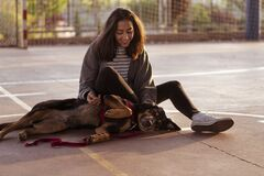 Young girl plays and pets her dog in a sports court, in the street.