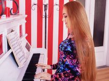 Young girl plays piano. The concept of lifestyle, music stock photo