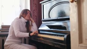 Young girl plays the piano - depressive concept. Close up stock video footage