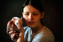 A young girl plays with piglet. A young girl plays with a newly born piglet in a village house on a summer day on a farm royalty free stock image