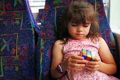 Young girl plays with Rubik`s Cube Royalty Free Stock Images