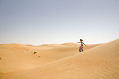 Young girl plays among sand dunes in desert Royalty Free Stock Image