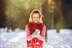 A young girl plays with snow. Winter evening Royalty Free Stock Photos