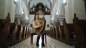 A young girl plays on a traditional Ukrainian instrument bandura in the church. A young girl plays on a traditional Ukrainian instrument - bandura in the old stock video