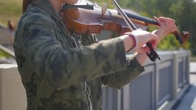 Young girl plays the violin on the promenade for tourists in the summer. Close up shot. Young girl plays the violin on the promenade for tourists in the summer stock video footage