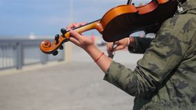 Young girl plays the violin on the promenade for tourists in the summer. Close up shot. Young girl plays the violin on the promenade for tourists in the summer stock footage