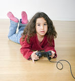 Young girl playstation. Little girl playing playstation lying on the floor Stock Photography