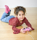 Young girl playstation. Little girl playing with playstation joystick lying on the floor Royalty Free Stock Photos