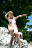 Young girl pointing. Young girl in summer clothing sitting on a rock in front of a tree pointing, caucasian/white Stock Images