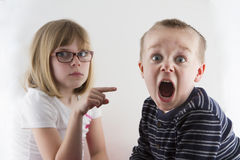 Young girl pointing at a boy. Boy got caught and now is in trouble and making a funny face Stock Photos