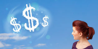 Young girl pointing at dollar sign clouds on blue sky Royalty Free Stock Photography