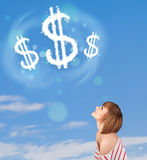 Young girl pointing at dollar sign clouds on blue sky Stock Photos