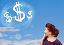 Young girl pointing at dollar sign clouds on blue sky Stock Photography