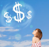 Young girl pointing at dollar sign clouds on blue sky Royalty Free Stock Images