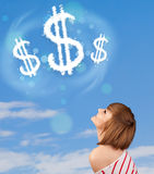 Young girl pointing at dollar sign clouds on blue sky Stock Image