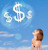 Young girl pointing at dollar sign clouds on blue sky Royalty Free Stock Photos