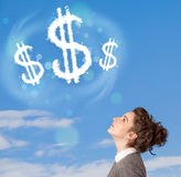 Young girl pointing at dollar sign clouds on blue sky Royalty Free Stock Image