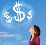 Young girl pointing at dollar sign clouds on blue sky Royalty Free Stock Photo