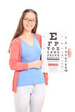 Young girl pointing on eyesight test with a stick Royalty Free Stock Photos