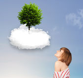 Young girl pointing at a green tree on top of a white cloud. Concept stock photos