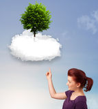 Young girl pointing at a green tree on top of a white cloud. Concept royalty free stock photos