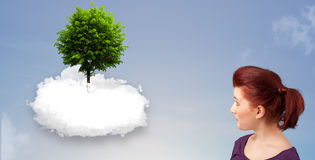 Young girl pointing at a green tree on top of a white cloud. Concept royalty free stock photography