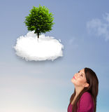 Young girl pointing at a green tree on top of a white cloud. Concept stock photo