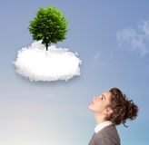 Young girl pointing at a green tree on top of a white cloud Stock Photos