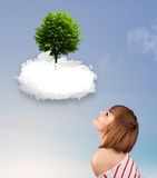 Young girl pointing at a green tree on top of a white cloud Stock Photo