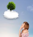 Young girl pointing at a green tree on top of a white cloud. Concept royalty free stock image