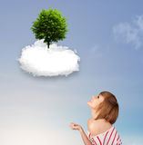 Young girl pointing at a green tree on top of a white cloud. Concept royalty free stock photo