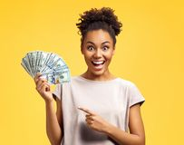Young girl points her forefinger to the money. stock photos