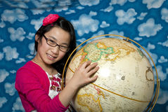 Young girl points to China on a globe Stock Photo