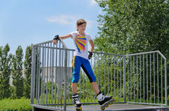Young girl poised at the top of a skating ramp Royalty Free Stock Images
